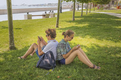 Young couple in a city park. Friendship, leisure, summer, technology and people concept - couple of smiling friends with smartphones sitting on grass in park Stock Photography