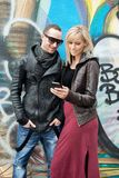 Young Couple in the City Smiling at Cellphone Stock Images