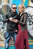 Young Couple in the City Smiling at Cellphone Royalty Free Stock Photo