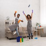 Young couple cleaning home, having fun with mop and broom. Housekeeping is fun. African-american couple dancing with mop and broom during spring cleaning at home stock image