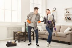 Young couple cleaning home, having fun. Young couple cleaning home, playing with mop and vacuum cleaner, having fun in living-room. Housekeeping and home stock image