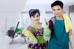 Young couple cleaning a mirror in the office Royalty Free Stock Photos