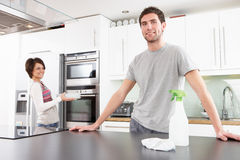 Young Couple Cleaning Modern Kitchen. Young Couple Cleaning A Modern Kitchen royalty free stock photo