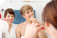Young couple cleaning teeth. Stock Images