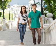 Young couple climbing a flight of outdoor stairs. Hand in hand up a steep hillside with a waterway and ferry visible behind them Royalty Free Stock Photos