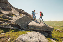 Young couple climbing in the mountains. Hiker couple helps each other to climb on the rock in mountains stock images