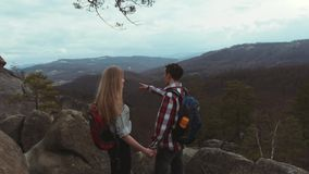 Young couple climbing the rocky hills, stylish young man with a backpack gives a hand to his beautiful girlfriend with a. Long hair, while moving to the top of stock video footage
