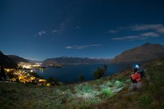 Young couple climbs up a hill to look at Queenstown, New Zealand at night stock image