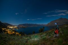 Night scene of young couple view queenstown, new zealand. stock photography
