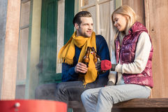 Young couple clinking beer bottles while sitting on wooden bench Stock Photography