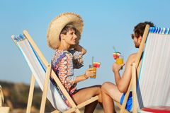 Young couple with cocktails in beach chairs acoast royalty free stock photography