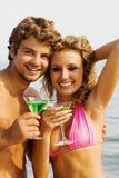 Young couple with cocktails on the seaside Stock Photos