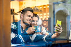 Young couple with coffee at the cafe in winter Royalty Free Stock Photo