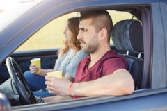 Young couple with coffee inside of car, have rest riding along road, happy family spend time together, travel on weekend, have stock images