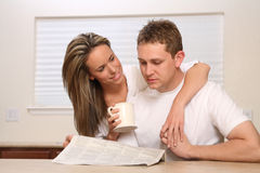 Young couple, coffee newspaper Royalty Free Stock Images