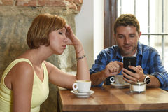 Young couple at coffee shop with internet and mobile phone addict man ignoring frustrated woman Royalty Free Stock Image