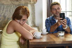 Young couple at coffee shop with internet and mobile phone addict man ignoring frustrated woman Stock Photo