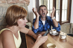 Young couple at coffee shop with internet and mobile phone addict woman ignoring frustrated man Royalty Free Stock Photography