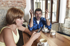 Young couple at coffee shop with internet and mobile phone addict woman ignoring frustrated man Stock Photo