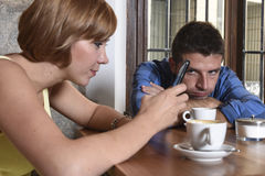 Young couple at coffee shop with internet and mobile phone addict woman ignoring frustrated man Stock Photos