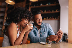 Young couple at coffee shop looking at smart phone royalty free stock photography