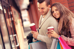 Young couple with coffee shopping in the mall. A picture of a joyful couple window shopping in the mall with coffee Royalty Free Stock Photos
