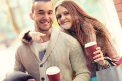 Young couple with coffee shopping in the mall. A picture of a joyful couple window shopping in the mall with coffee Royalty Free Stock Photography