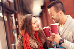 Young couple with coffee shopping in the mall. A picture of a joyful couple window shopping in the mall with coffee Royalty Free Stock Images