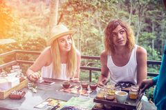 Young couple coffee and tea tasting during sunset in the jungle rainforest of a tropical Bali island. royalty free stock image