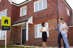 Young Couple Collecting Keys To New Home From Realtor royalty free stock photos