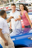 Young couple collecting new car. Young coupled collecting new car from salesman Stock Photos