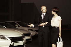 Young couple collecting new car at dealership lot stock images