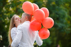 Young couple with colourful balloons in town. Royalty Free Stock Photography