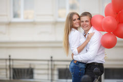 Young couple with colourful balloons in town. Stock Image