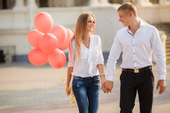 Young couple with colourful balloons in town. Royalty Free Stock Photos