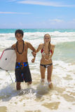 Young couple comes out of the ocean. A young couple comes out of the ocean with a boogie board at Kailua Beach, Hawaii Stock Photo