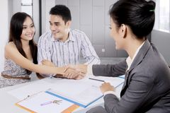 Young couple hand shaking businesswoman Stock Photos