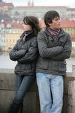 Young Couple Conflict. Young couple on an ancient bridge in Prague, offended, the man and the woman looking to the opposite sides, angry faces Stock Photo