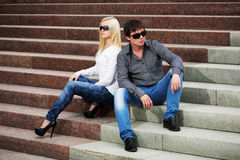 Young fashion couple in conflict sitting on the steps Royalty Free Stock Photos