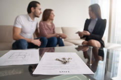 Young couple considering first mortgage, loan agreement for purc. Young family couple sitting on sofa discussing first mortgage with agent, focus on loan Royalty Free Stock Photos