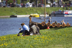 The young couple considers the Vikings ship which has appeared on the river. royalty free stock photography