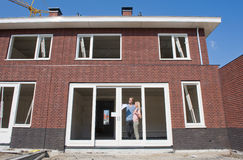 Young couple on construction site. ENSCHEDE, NETHERLANDS - APR 19: Young couple with blueprint is looking happily outside to the view from their new home, April Stock Image