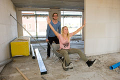 Young couple on construction site. ENSCHEDE, NETHERLANDS - APR 19: Young couple is happy and having fun with a wheelbarrow in their new built home, April 19 Royalty Free Stock Photo