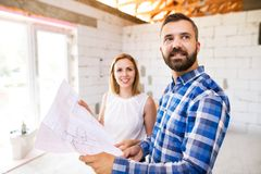 Young couple at the construction site. A men and women looking at plans of the new house, discussing issues at the construction site Royalty Free Stock Photo