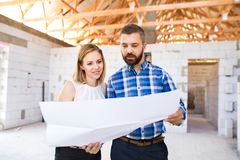 Young couple at the construction site. A men and women looking at plans of the new house, discussing issues at the construction site Stock Images