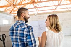 Young couple at the construction site. A men and women looking at plans of the new house, discussing issues at the construction site Royalty Free Stock Photos