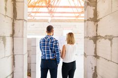 Young couple at the construction site. A men and women looking at plans of the new house, discussing issues at the construction site. Rear view Stock Photos