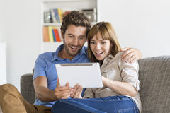 Young couple consult the results of the lottery on app tablet pc Royalty Free Stock Photos