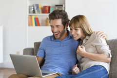 Young couple consult the results of the lottery on laptop in modern apartment Royalty Free Stock Image