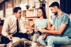 Young Couple Consulting With Furniture Seller. royalty free stock photo